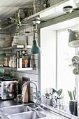 Offene Edelstahlregale für Küchenzubehör daneben Edelstahlspüle vor Küchenfenster