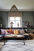 Corner sofa and ethnic accessories in interior with grey walls