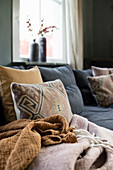 Scatter cushions and blankets on comfortable corner sofa