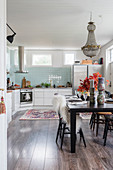 Kitchen with pale blue wall tiles, dark wooden floor and black dining table