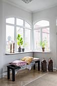 Cushions and fur rug on black bench in corner below windows