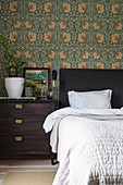 Double bed and bedside table against wall with William Morris wallpaper