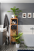 Bathroom accessories on wooden shelves between washstand and free-standing bathtub
