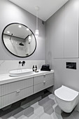 Washstand with drawers, oval mirror and toilet in bathroom