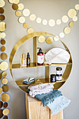 Golden garland above round shelving unit containing bathroom supplies