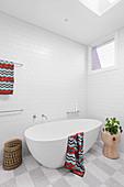 Freestanding bathtub on checkerboard floor in the bathroom in white