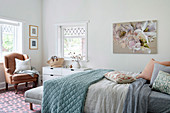 Double bed with pillows and bedspread and antique leather armchair in the bedroom
