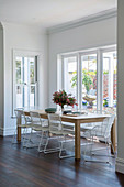 Filigree white chairs on the wooden table in front of the window to the garden