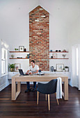 Man at large desk in front of fireplace with exposed brickwork