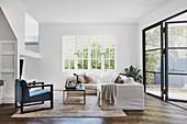 Wohnzimmer mit weißem Sofa und Fensterfront zum Garten