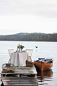 Laid table on a jetty and boat on a lake