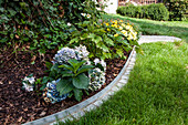 DIY metal and stone edging around flowerbed