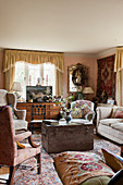 Armchairs and sofa grouped around antique wooden trunk used as coffee table