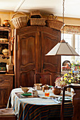 Wicker baskets on top of old wooden cupboard in kitchen of English country house