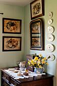 Bürstensammlung auf Antik-Kommode in Zimmerecke, darüber Spiegel und antike Blumenbilder