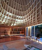 Offener Wohnraum mit Essbereich vor Küche in Kupfer und mit trichterförmigem Dach