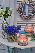 Cornflowers, hydrangeas and candle lanterns on garden table