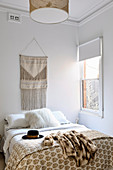 Beige ethnic wall hanging over bed with white fur pillow