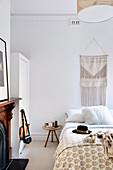 Bedroom in light beige tones with ethnic wall hangings over bed