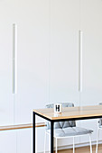 Wooden table with black metal frame in front of plain white wall unit