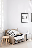 Sitting area with beige upholstered armchair, wooden stool and side table