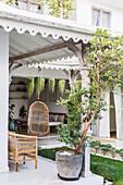 Überdachte Terrasse am exotischen Haus mit sommerlichem Garten