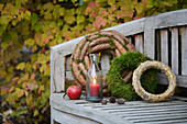 Garden bench decorated with wreaths (moss, fir cones and straw) and candle lantern