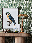 Lamp in the shape of a palm tree and picture of a parrot in front of wallpaper with palm tree motifs
