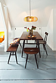 Dining table, stool, chair and bench below sloping ceiling