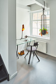 Glass table in niche between window and foot of staircase in renovated Dutch townhouse