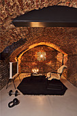 Exercise equipment and cosy seating area in renovated vaulted cellar
