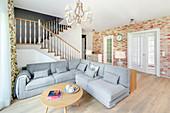 Graues Sofa im offenen Wohnraum mit Treppe und Backsteinwand