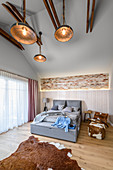 Exposed roof structure and cowhide accessories in bedroom