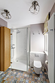 Shower and toilet in bathroom with colourful patterned floor tiles