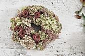 Handmade hydrangea and rose wreath on white shabby-chic table