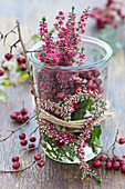 Preserving jar with budding heather in a heart shape and hawthorn berries