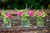 Rural bouquets of roses, lady's mantle and meadow flowers in mason jars