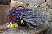 Rustikaler Korb mit Lavendelblüten vor Steinmauer