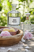 Homemade herbal distillate of rose for use as facial toner in bottle on wooden table