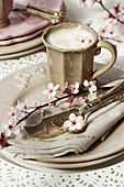 Beige arrangement with cup of cappuccino and sprig of blossom
