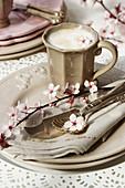 Tasse Cappuccino auf Gedeck in Beige mit Blütenzweig