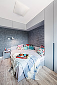 Grey bedroom with high wall-mounted cabinets above bed