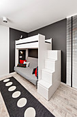 Steps with storage spaces leading to loft bed in black-and-white teenager's bedroom