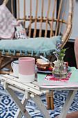 Sandwiches, Kaffeebecher, Zeitschriften und Blumenvase auf Klapptisch im Freien