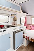 Hellblauer Küchenbereich in liebevoll renoviertem 80er-Jahre Wohnwagen