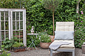 A quiet corner in the garden with a sun lounger, antique window, and decorations