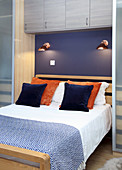 Double bed with reading lamps on purple wall and wall-mounted cupboards