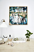 Stones and crystals, leaf branch and table lamp, paintings above