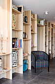 Armchair against floor-to-ceiling wooden shelves in living space with tiled floor