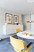 Offener Essbereich mit rundem Tisch, Freischwinger, Hängeschrank und Kunstwerken an den Wänden